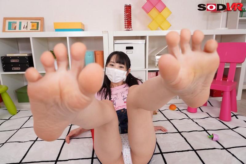 マスクの女子が足裏を広げて見せてます