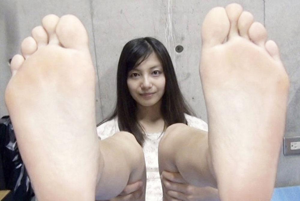 女子が両方の足裏を見せてます